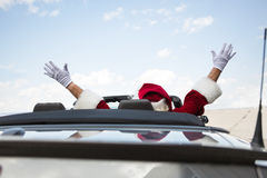 Santa With Arms Raised In Convertible Against Sky Stock Photo