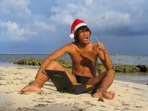 Santa asiático en la playa con la computadora portátil Foto de archivo libre de regalías
