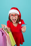 Santa asian woman holding shopping bags and credit card against Royalty Free Stock Photo