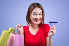 Santa asian woman holding shopping bags and credit card against Stock Photos