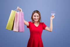 Santa asian woman holding shopping bags and credit card against Stock Image