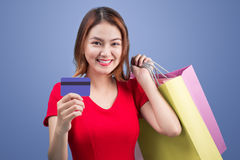 Santa asian woman holding shopping bags and credit card against Royalty Free Stock Photos