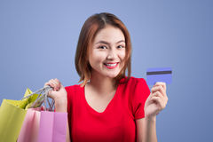 Santa asian woman holding shopping bags and credit card against Stock Photography