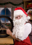 Santa Assemblying Bicycle in Workshop Royalty Free Stock Images