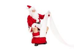 Santa assentou no toalete e em ler um papel Fotografia de Stock Royalty Free
