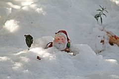 Santa avalanche. Santa clause statue under the snow Royalty Free Stock Photo