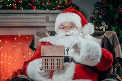 Santa avec le modèle et la clé de maison photographie stock