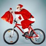 Santa avec le sac rouge sur la bicyclette photo libre de droits
