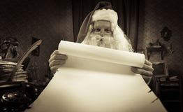 Santa avec une longue liste de Noël Photographie stock libre de droits