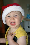 Santa Baby. A little girl, wearing a bright red santa hat and a very adorable grin stock image