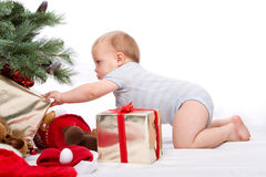 Santa Baby boy reaching for Christmas gift. Baby boy reaching for Christmas gifts. Studio shoot on white background Stock Photography