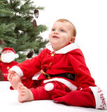 Santa Baby boy sitting next to Christmas tree. Royalty Free Stock Photos