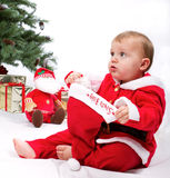 Santa Baby boy sitting next to Christmas tree. Stock Photos