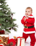 Santa Baby boy standing next to Christmas tree. Studio shoot on white background Royalty Free Stock Image