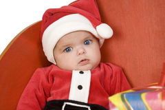 Santa baby dressed. A baby dressed as Santa Claus sitting in a sleigh stock photo