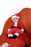 Santa baby dressed. A baby dressed as Santa Claus sitting in a sleigh stock photography