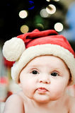 Santa Baby FAce. Serious Baby Girl in santa outfit for christmas Royalty Free Stock Photo
