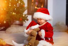 Santa baby playing with a teddy stock image