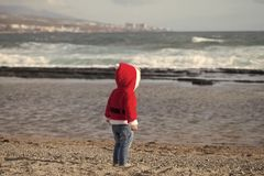 Santa baby in red costume walking barefoot on sea beach stock images