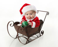 Santa baby sitting in a sleigh. Adorable young baby wearing a santa claus suit and hat sitting in a metal Christmas snow sleigh holding an ornament Stock Photos