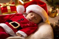 Santa baby sleeping with Christmas presents at living room Royalty Free Stock Images
