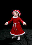 Santa Baby Standing. Pretty little girl dressed in a Santa-style dress and hat, standing with her arms out stretched and smiling Royalty Free Stock Photography
