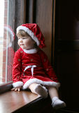 Santa Baby at Window. Pretty little girl sitting at a large, old fashioned window, wearing a santa-style dress and hat Royalty Free Stock Image