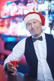 Santa in bar. Serious man in Santa cap looking at camera in the bar Royalty Free Stock Photos