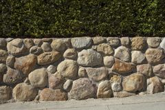 Santa Barbara sandstone fieldstone wall. Horizontal detail view of a sandstone wall with a green hedge above Stock Images