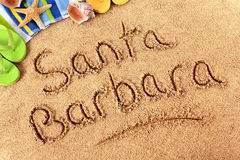 Santa Barbara beach sign sand writing. The words Santa Barbara written on a sandy beach wih beach towel, starfish and flip flops Stock Photography