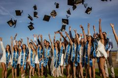 SANTA BARBARBRA, CALIF, EUA, o 8 de junho de 2018 - os amigos de graduação jogam seus tampões da graduação no ar fotografia de stock royalty free