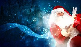 Christmas theme with santa. Santa with beard and red hat holding and looking into the sack Stock Photography