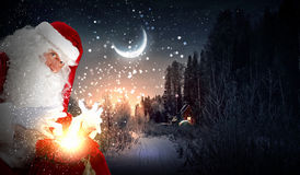 Christmas theme with santa. Santa with beard and red hat holding and looking into the sack Stock Image