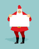 Santa with  blank sheet of white hands. Christmas character hold Royalty Free Stock Photography