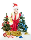 Santa blond girl sits between two firs Stock Photography