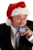 Santa blowing party toy. Middle age man wearing a Santa hat, blowing a party favor or toy Stock Images