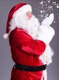 Santa blows off snowflakes stock photography
