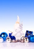 Santa on blue background. Cute santa claus figure with christmas balls on gradiant background Stock Photos