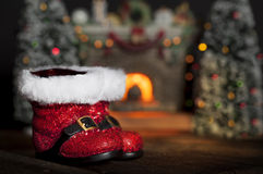 Santa Boots Fireplace. Christmas Santa boots with burning fireplace and Christmas trees blurred in background royalty free stock image