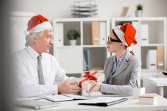 My best regards. Santa boss giving box with gift for Christmas to young businesswoman with best regards on holiday royalty free stock images