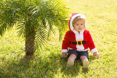Santa boy at green palm tree. Small santa claus cute boy or child in red new year coat with white fur and hood celebrates christmas or xmas holidays near green Royalty Free Stock Images