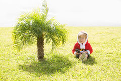 Santa boy at green palm tree. Small santa claus cute boy or child in red new year coat with white fur and hood celebrates christmas or xmas holidays near green Stock Image