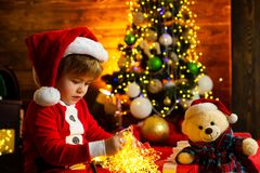 Santa boy little child celebrate christmas at home. Family holiday. Boy cute child cheerful mood play near christmas. Tree. Merry and bright christmas. It is royalty free stock photography
