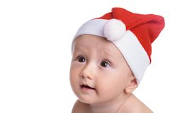 Santa boy looking amazed. Baby boy isolated on white, with a red cap, looking amazed and full of expectations to the side Royalty Free Stock Photography