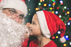 Santa and boy near the decorated Christmas tree. Wishes list Royalty Free Stock Photos