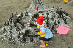 Santa boy with sandy castle royalty free stock photography