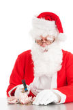 Santa breaking his piggy bank royalty free stock photo