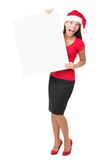 Santa business woman holding banner sign. Christmas woman showing blank sign billboard standing in full length wearing Santa hat. Santa woman portrait of an Stock Photos