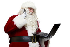 Santa is Busy!. Santa Claus (isolated on white) looking at his laptop while on his cell phone Royalty Free Stock Photos