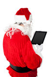 Santa busy in operating tablet pc Stock Photography